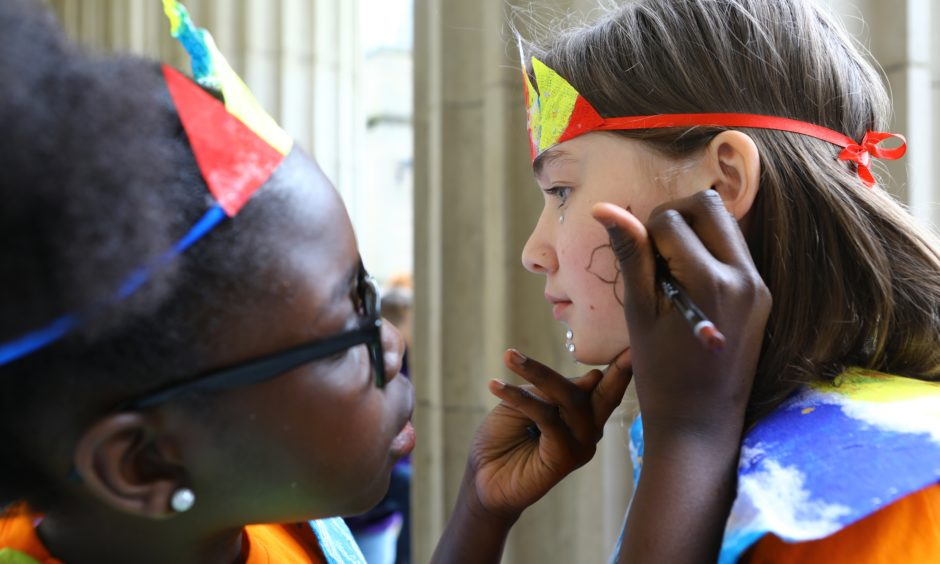 Salimatah Drammah puts the finishing touches to Lilly Webster's face. They are from the Douglas Library group.