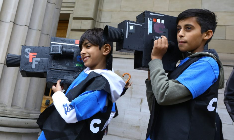 Budding camaramen Ayyan Yaqub and Shahzaib Iqbal take part in the Dundee Design Parade.