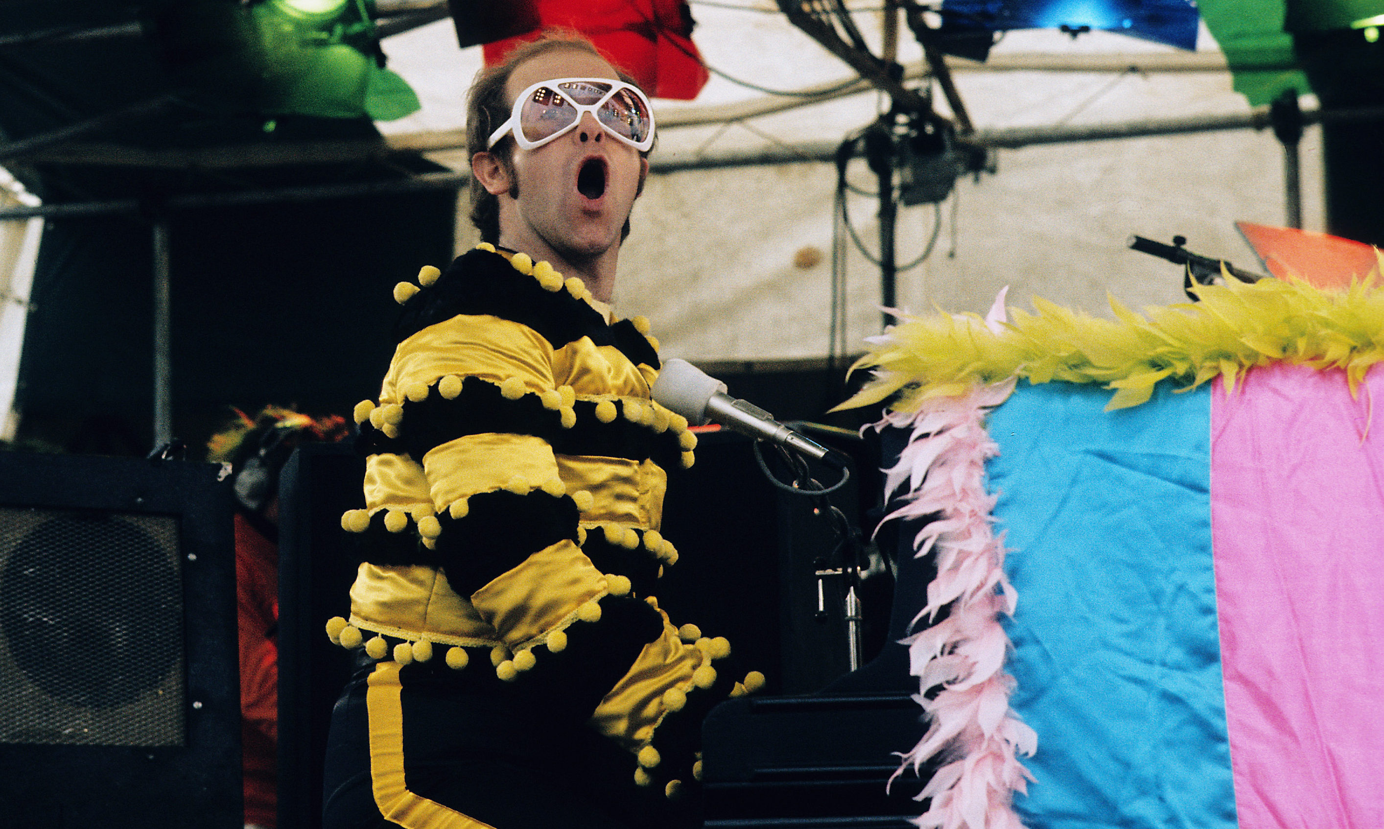 Elton John performs at an open-air concert in May 1974 in Watford, England.