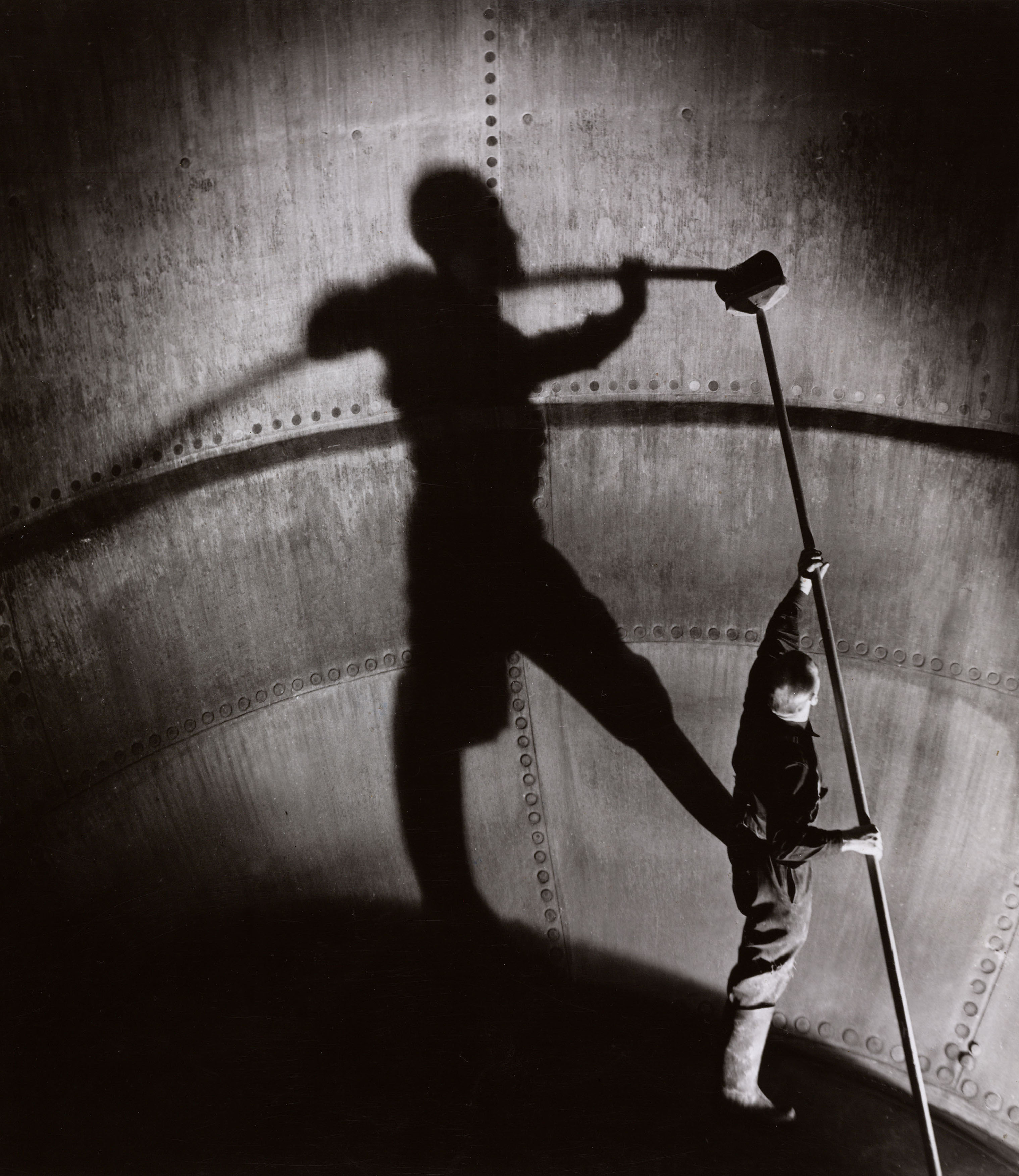A brewery worker casts a giant shadow as he cleans inside a copper coffer. Taylor-Walker Brewery, Manchester.