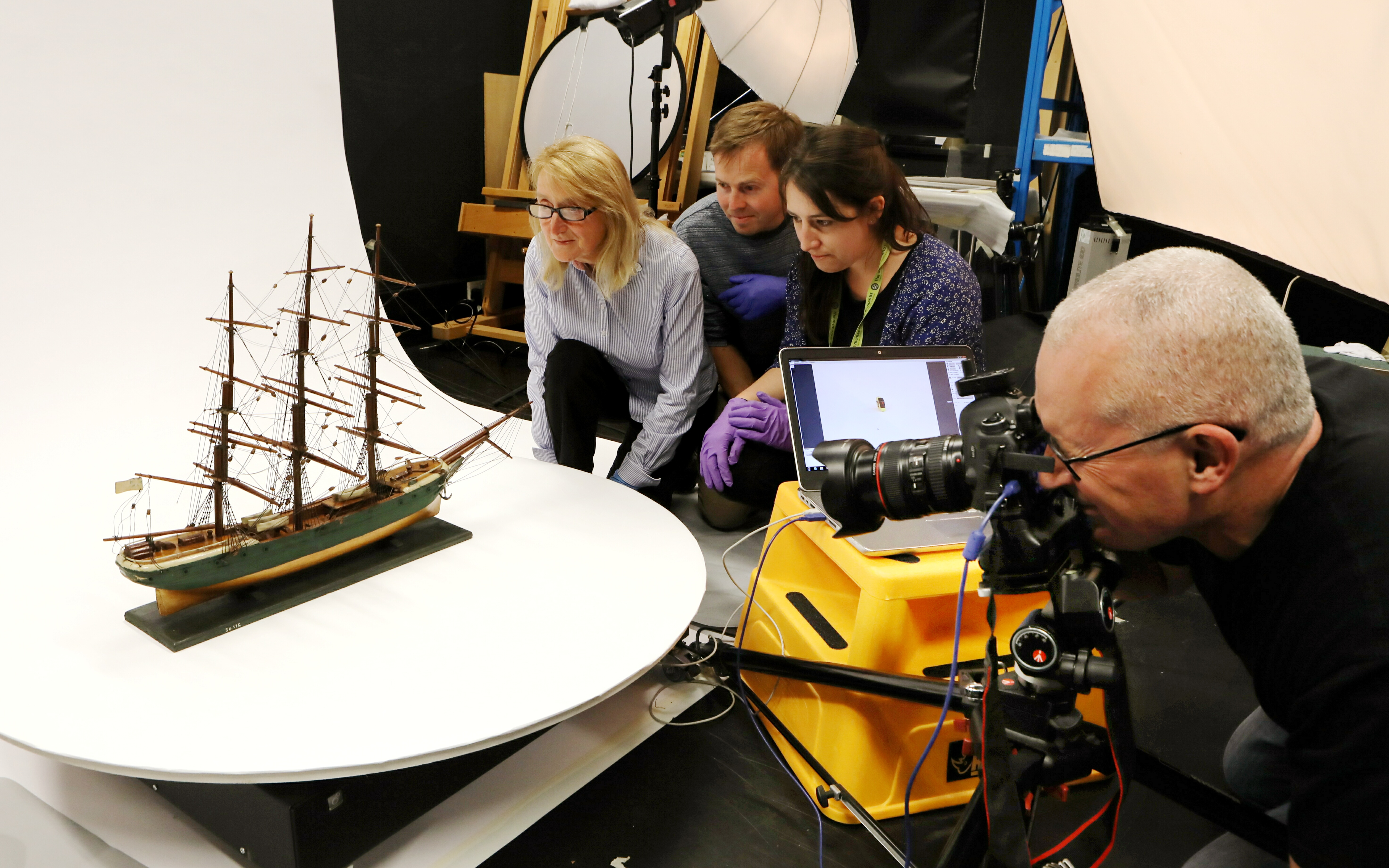 Staff work on capturing images of a three-masted ship — one of 139 in the collection