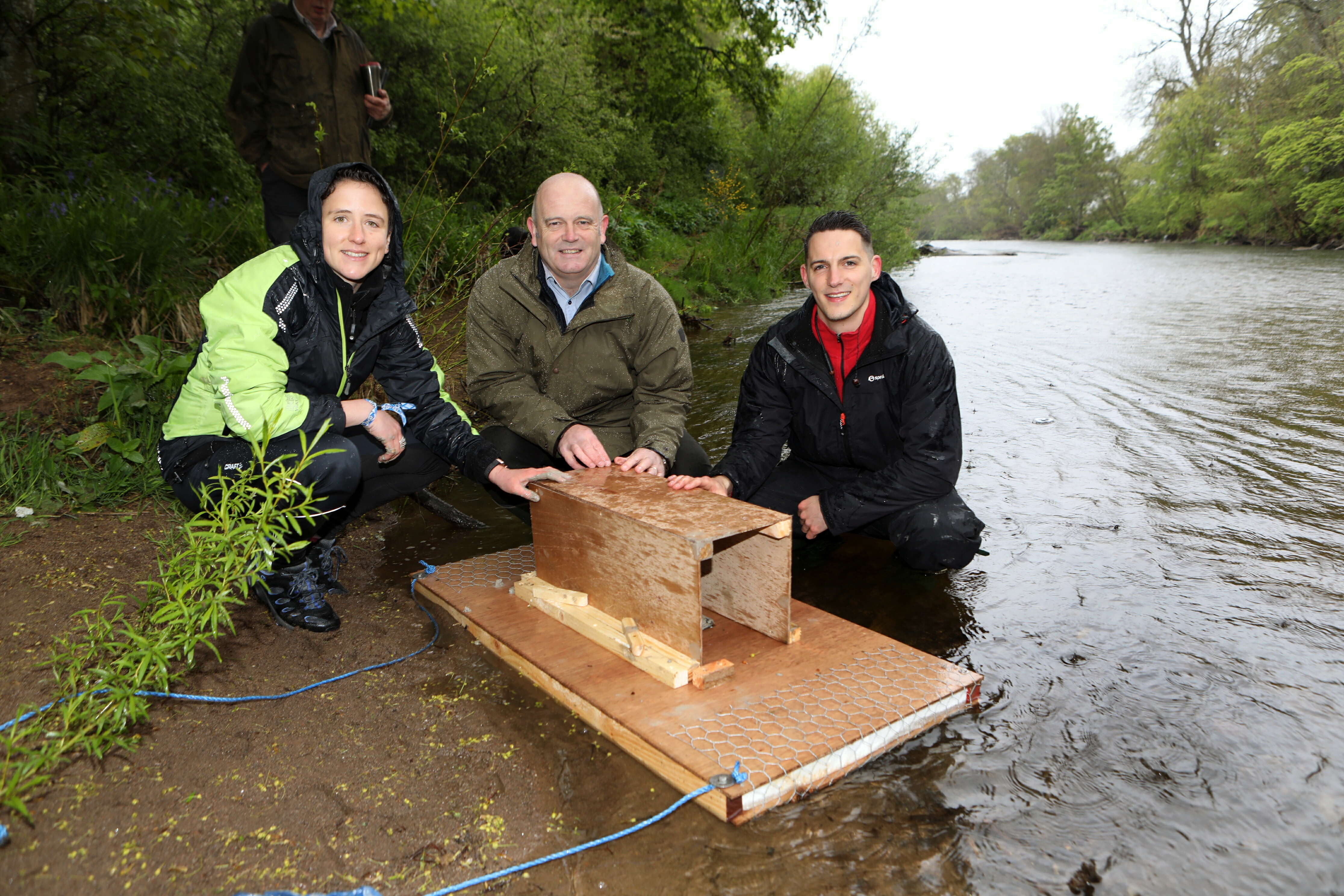 MSP Mairi Gougeon  laying a mink monitoring station with SISI project officer Mark Purrmann-Charles and SISI project manager, Callum Sinclair