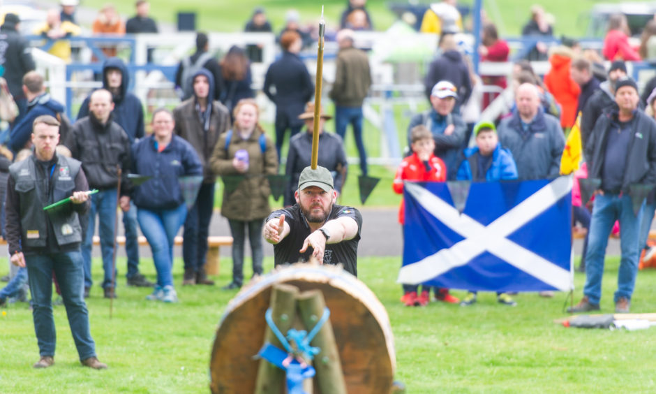 Competitors aim to hit a target with their axes, getting as close to the bullseye as possible.