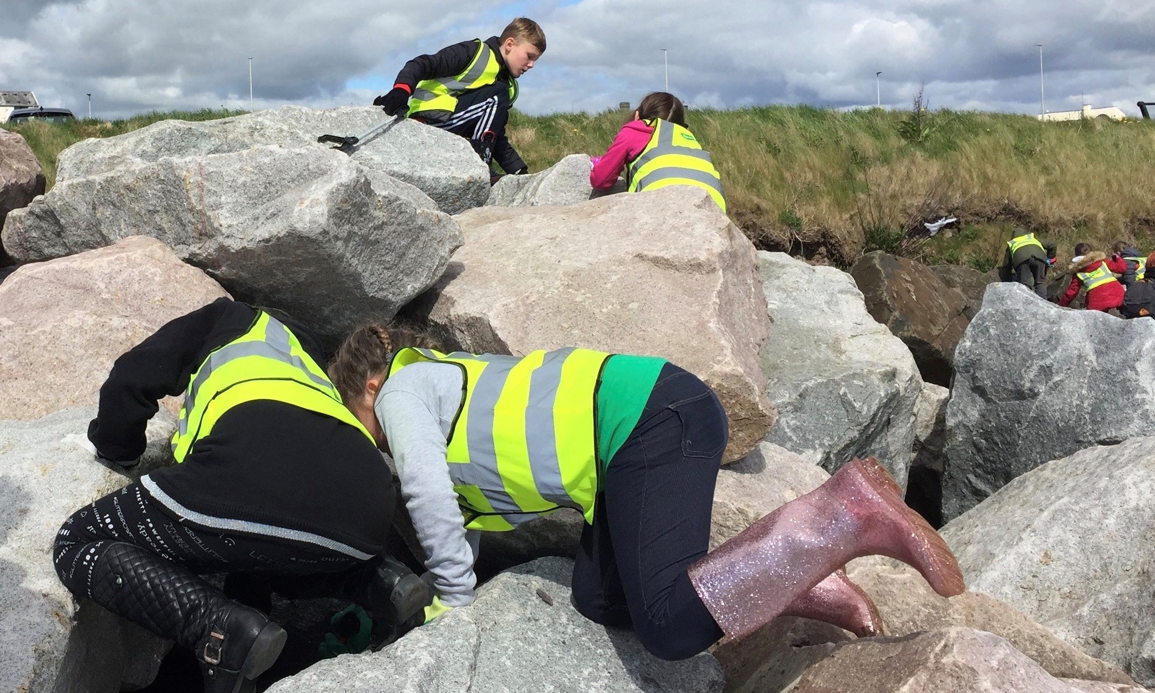 Children from Ladyloan Primary School pulling litter from rock armour during the Great Angus Beach Clean. Pic supplied.
