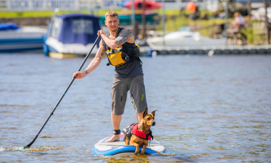 Ray Will and dog Eiger on Ray's Stand Up Paddle Board on Loch Tay, Kenmore.