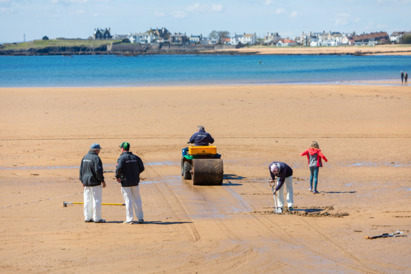 The cricket pitch is crated once the tide has receded by Ship Inn players, Graham Bucknall and Iain Murdoch.