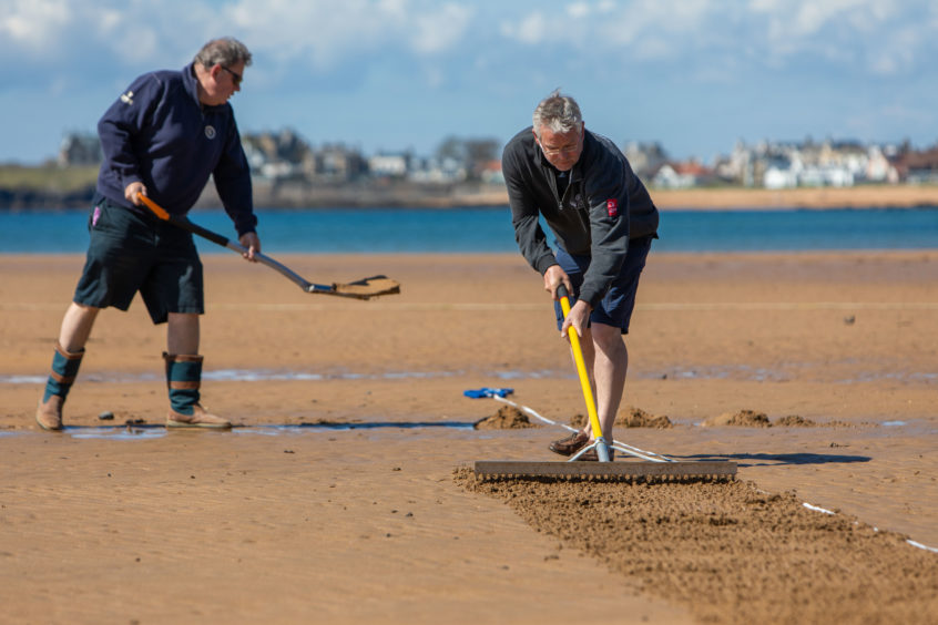 1st Game of Season at Elie for Beach Cricket.The cricket pitch is crated once the tide has receded by Ship Inn players, Graham Bucknall and Iain Murdoch