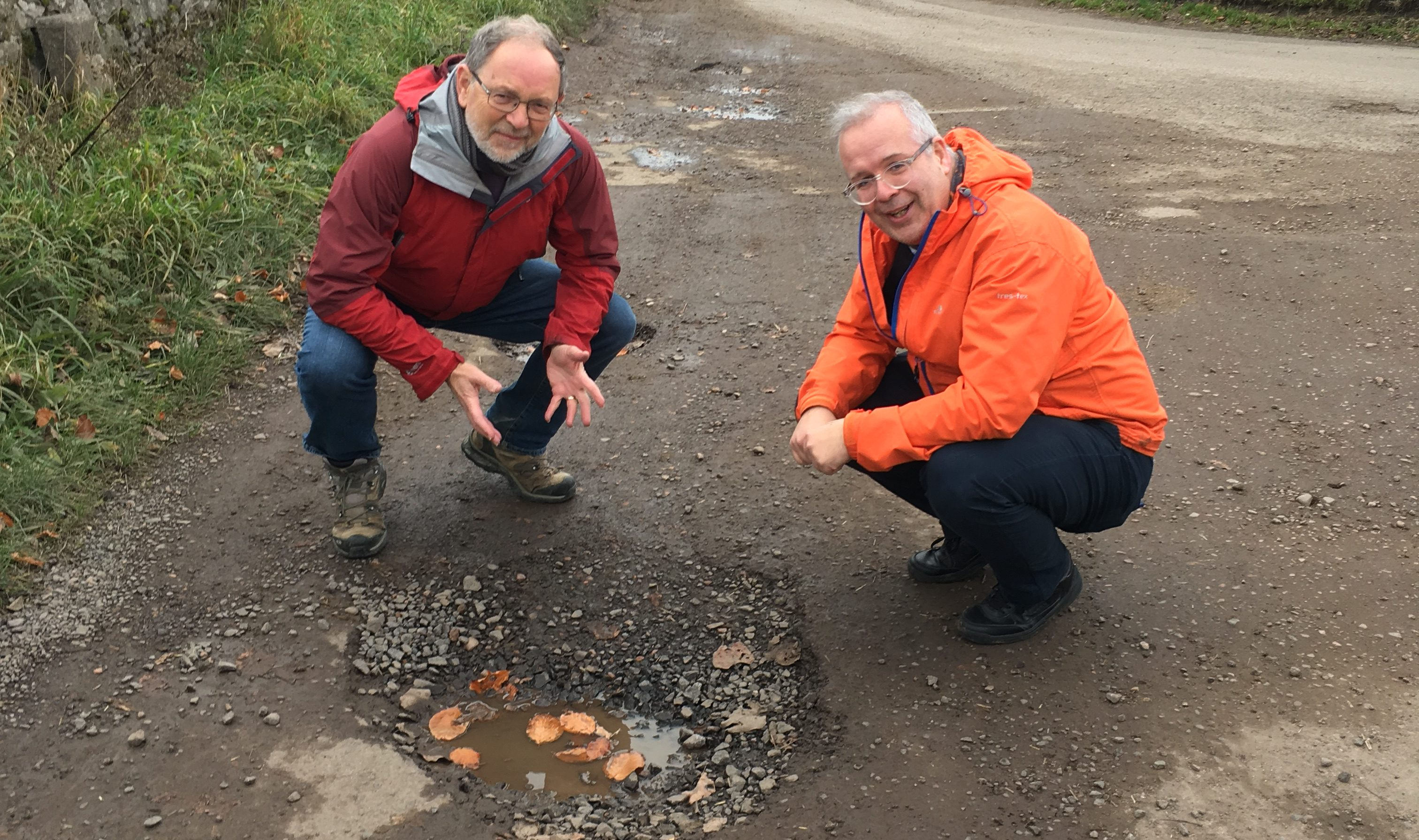 Mr Tepp, right and Councillor Tim Brett survey a large pothole