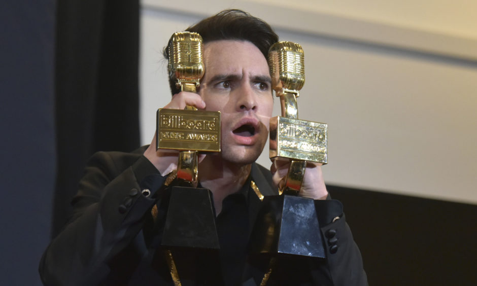 "Brendon Urie, of Panic! at the Disco, poses in the press room with the awards for top rock album for ""Pray For The Wicked"" and top rock song for ""High Hopes"" at the Billboard Music Awards."