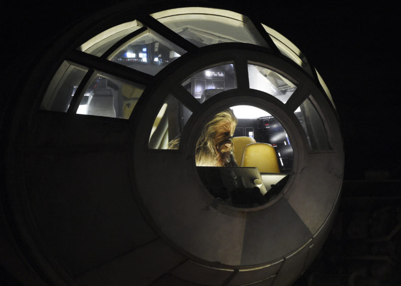 """The """"Chewbacca"""" character from the """"Star Wars"""" film franchise sits in the cockpit of the Millennium Falcon starship during a dedication ceremony for the new Star Wars: Galaxy's Edge."""