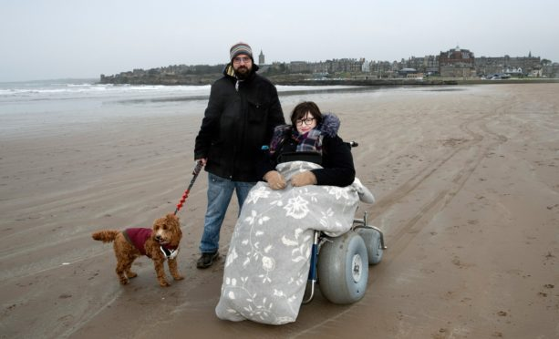 Sarah Lux using one of St Andrews beach wheelchairs with her partner Ian Martin and dog 'Teddy' on the West Sands.