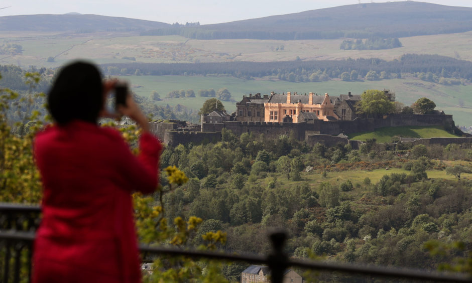 A person takes a picture of Stirling Castle in Scotland during the warm weather.