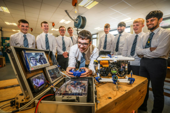 S6 pupil Aidan McIrvine, 17, and other pupils who are taking part in the competition with one of their machines named 'Discovery.'