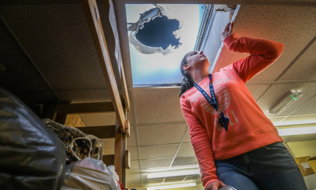 Colleen Mackie, assistant manager, looking up to the damage in the roof.