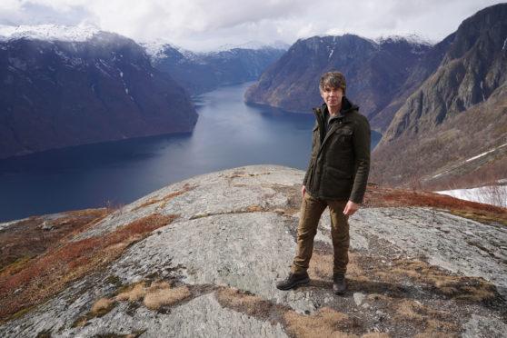 Professor Brian Cox on location at Stegastein, overlooking Aurlandsfjorden in Norway.