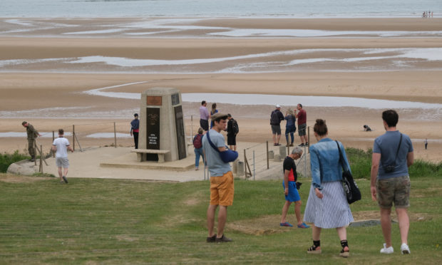 Visitors walk toward a monument to the soldiers of a US unit killed in the D-Day assault at Omaha Beach in Normandy on June 02, 2019 near Colleville-sur-Mer, France.