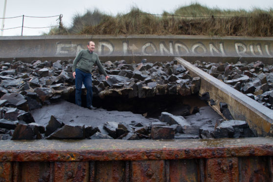 Councillor Bill Duff inspecting the damage at Montrose beach.
