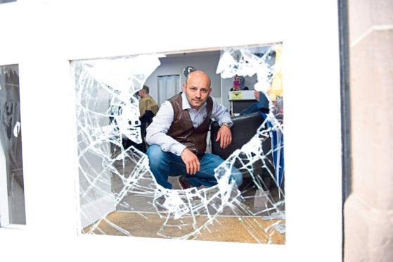 Sinan Durmus, owner of the Turkish Barbers, surveys the damage at his salon