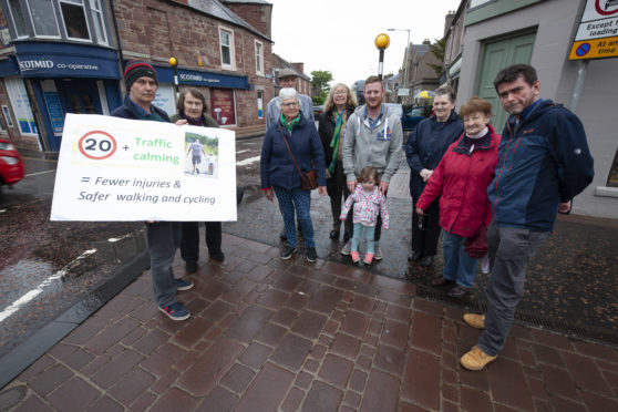 Locals in Coupar Angus promote their 20 MPH speed campaign at the Cross, Organiser Michael Gallagher holding sign