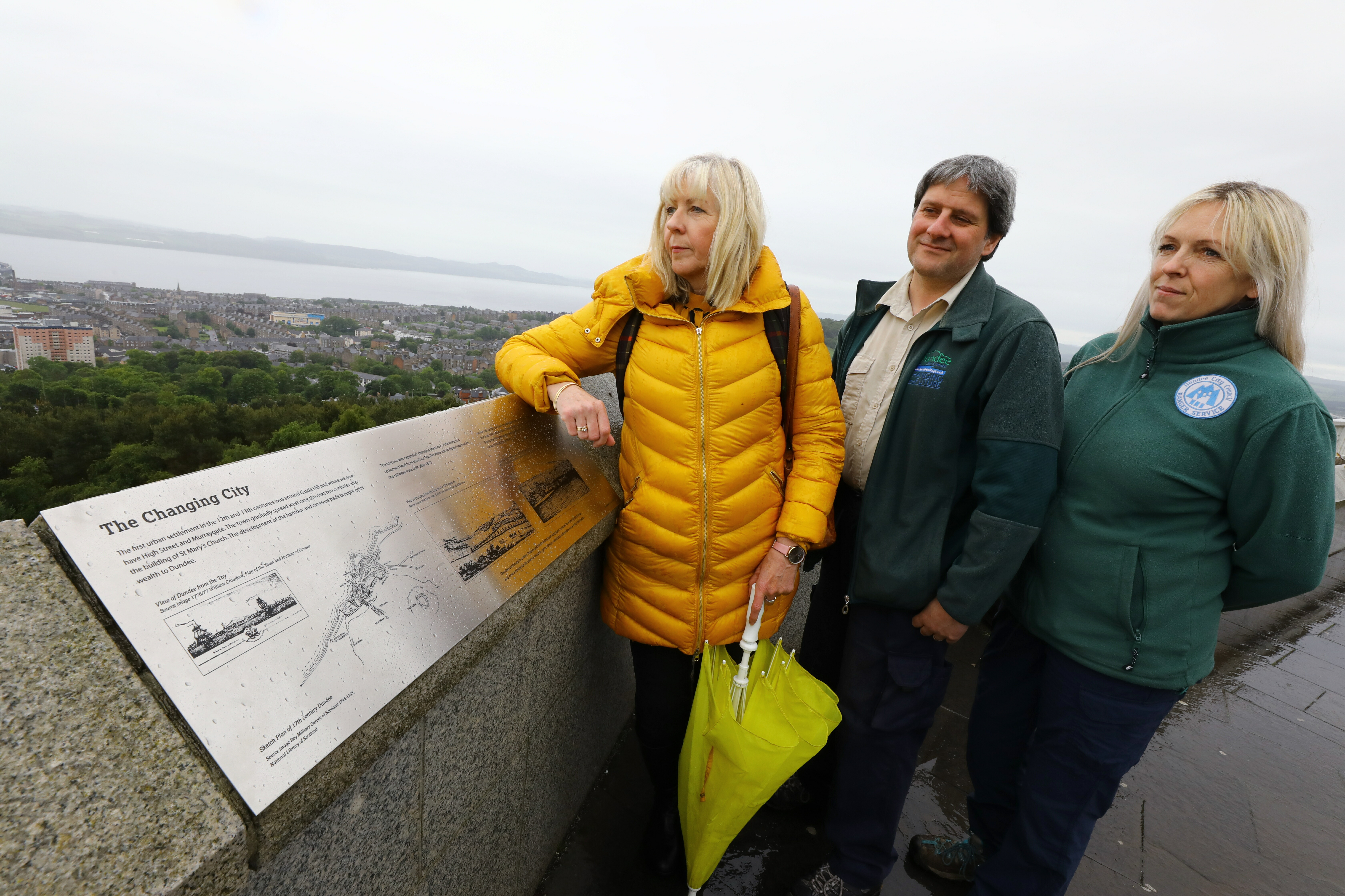 Councillor Anne Rendall, Colin Donald and Laura Jane Blackie, who illustrated the plaques, - both DCC Countryside Rangers, beside one of the new plaques at the top of Dundee Law.