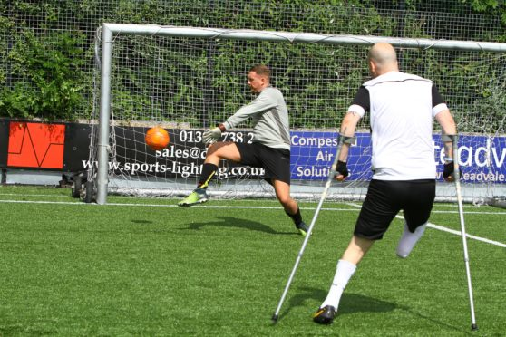 Rob Wilson firing in a shot with Steven Tully in goal, at the Amputee Football Programme training session at the GA Arena in Dundee