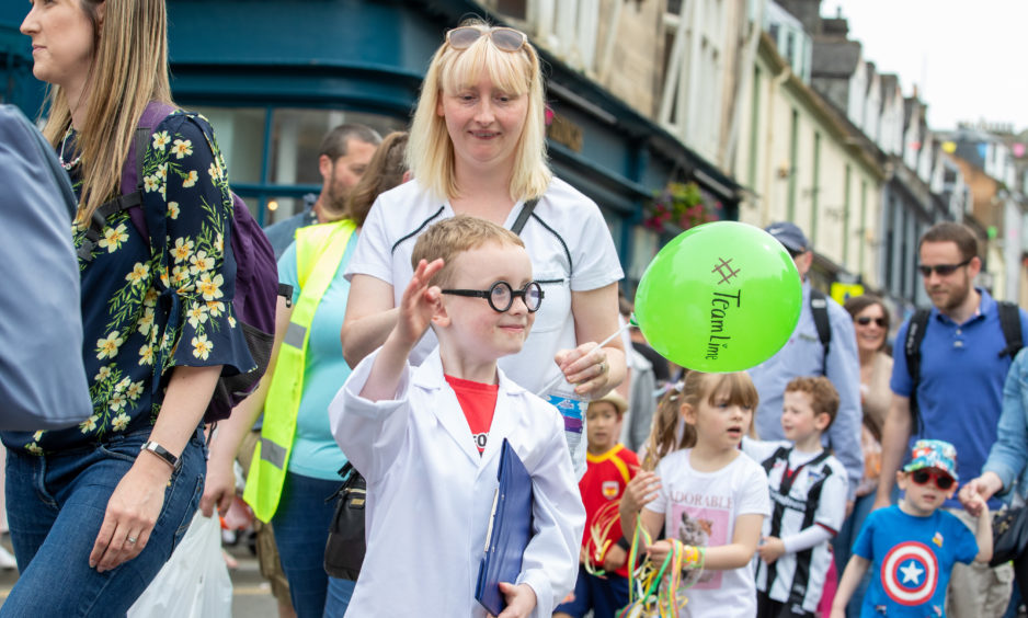 One mini scientist waves to the crowds.