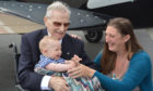 Flight Lieutenant Ernie Holmes DFC, meeting his great-grandson Henry for the first time at Coventry Airport, with Henry's mother Laura, as part of Project Propeller, an annual gathering of World War Two aircrew veterans.