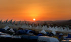 Festival goers watch the sunset during day two of Glastonbury Festival at Worthy Farm, Pilton on June 27, 2019 in Glastonbury, England.