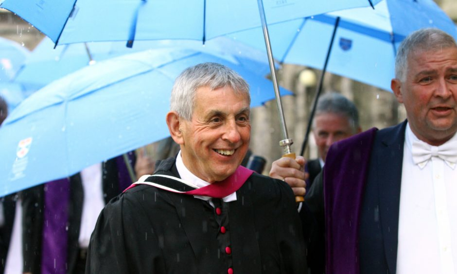 Sir Ian McGeechan smiles despite the rain.