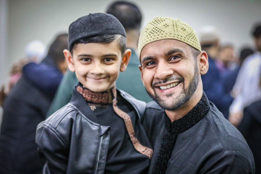 A father and son (on his first visit to the Mosque) after prayers and celebrations at Dundee Islamic Society mosque to celebrate Eid.