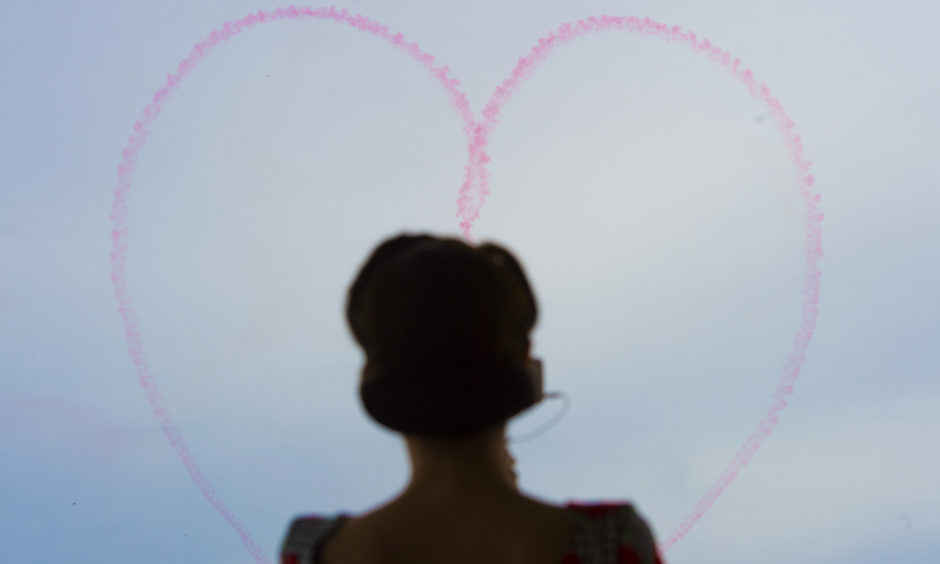 A member of the D-Day Darlings watches the Red Arrows from the MV Boudicca at Portsmouth.