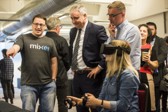 Gary McCartan (left), CEO of Pocket Sized Hands demonstrates a games project to Richard Lochhead MSP and Director of InGAME Sean Taylor