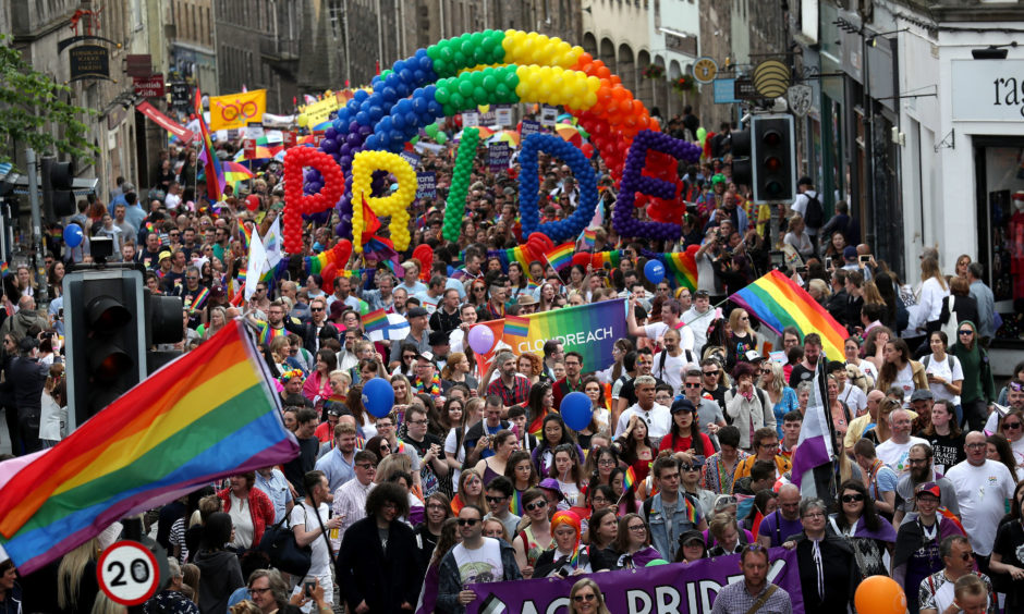 Pride marchers march up the Royal Mile in Edinburgh.
