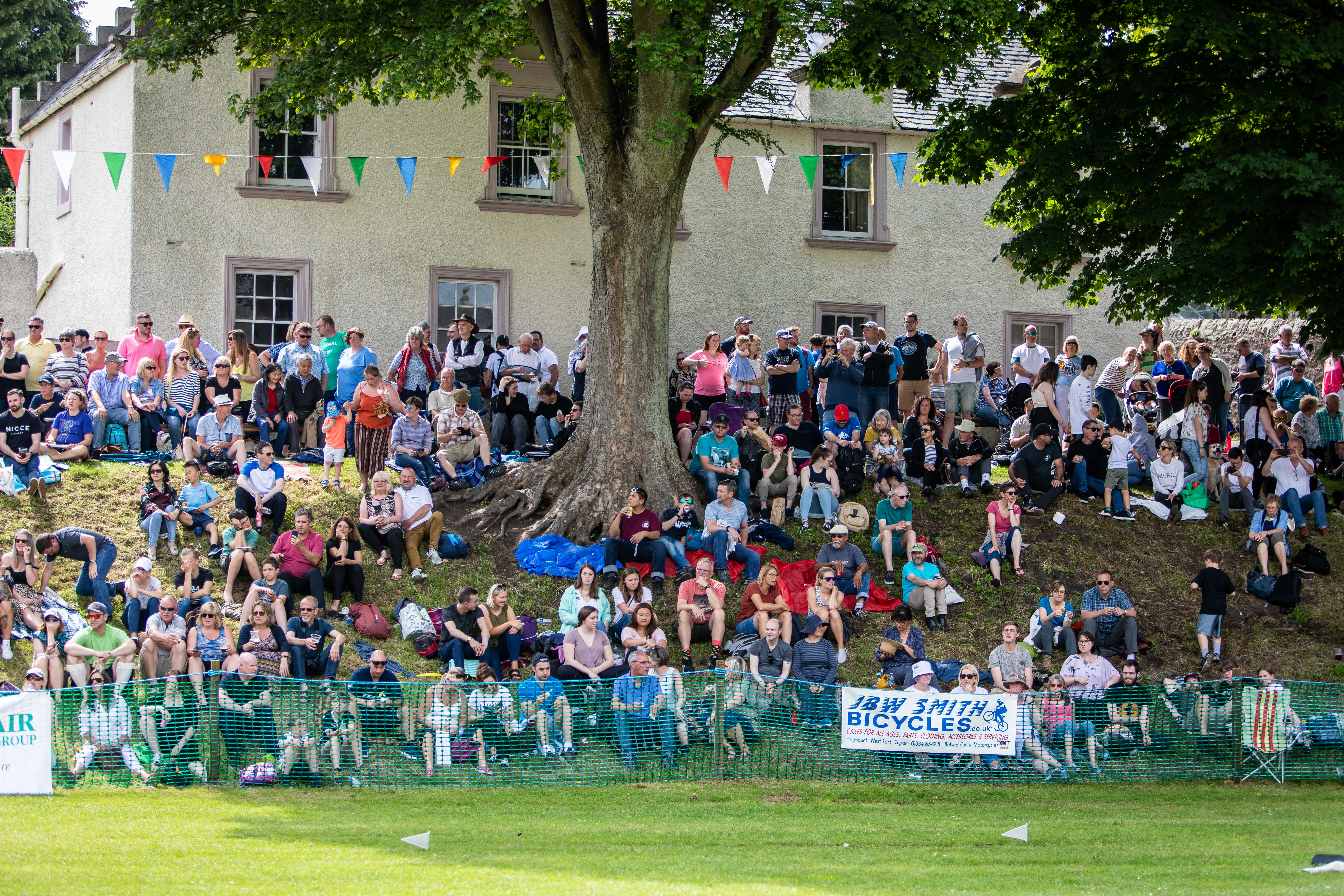 Crowds gather on the banks in the scorching heat of summer to watch Ceres Highland Games.