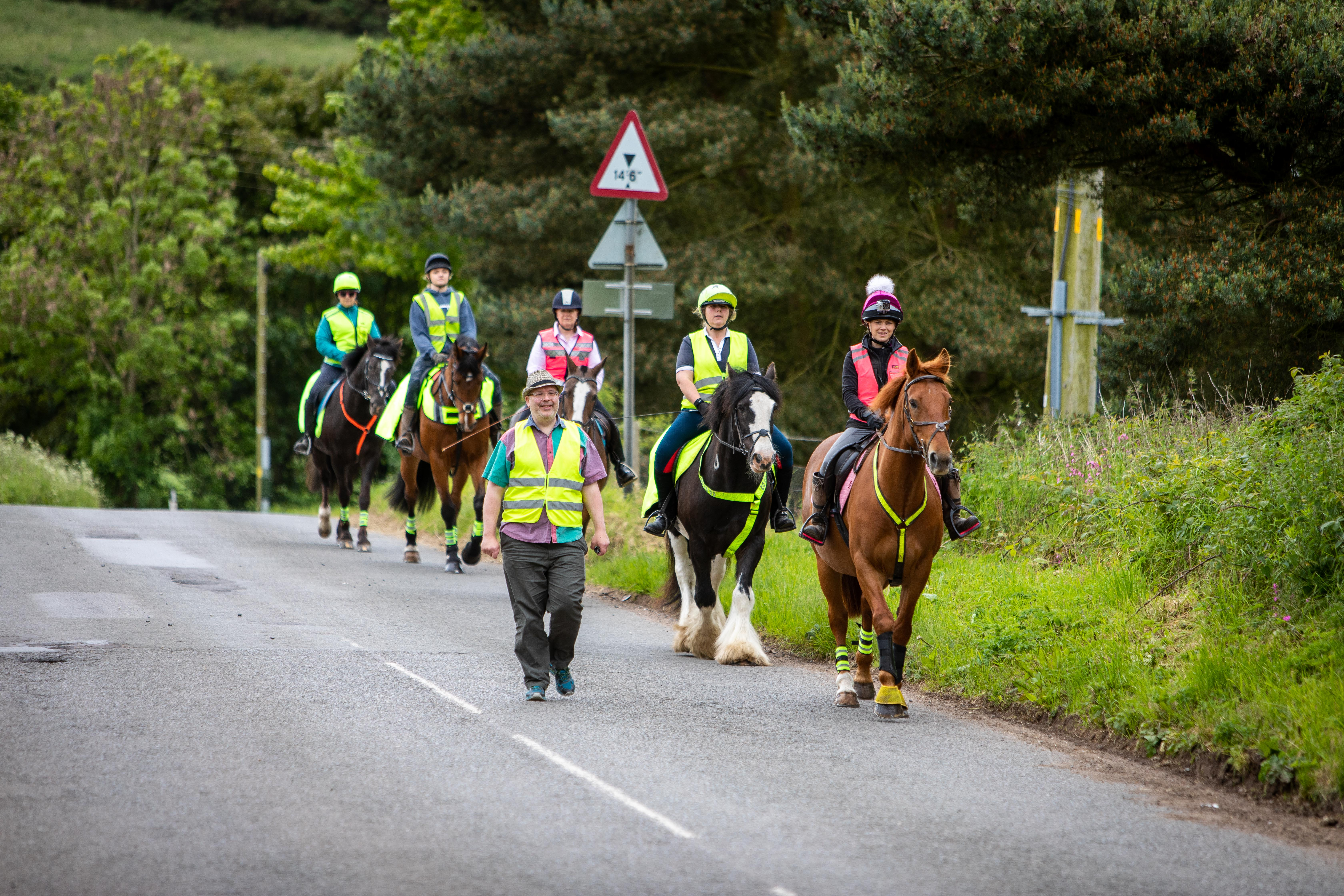 Newton Farm Stables manager Caroline Andrew and Councillor Jonny Tepp leading horses on a country road.