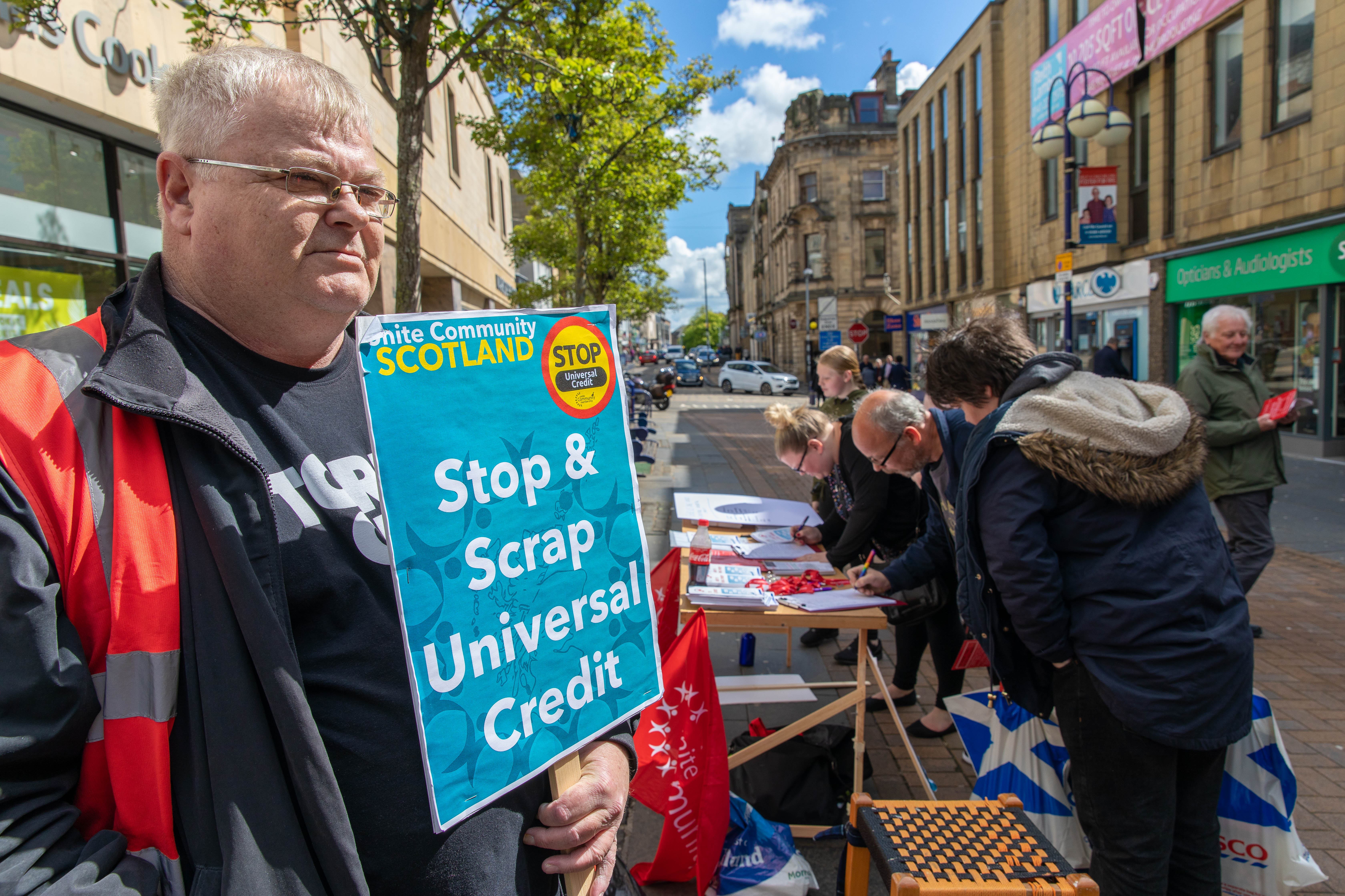 John Gillespie of Unite the Union holds a placard as people signed an Anti Universal Credit petition earlier this month.
