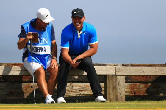 Brooks Koepka and caddie Ricky Elliott share a joke during practice for the Open Championship at Royal Portrush.
