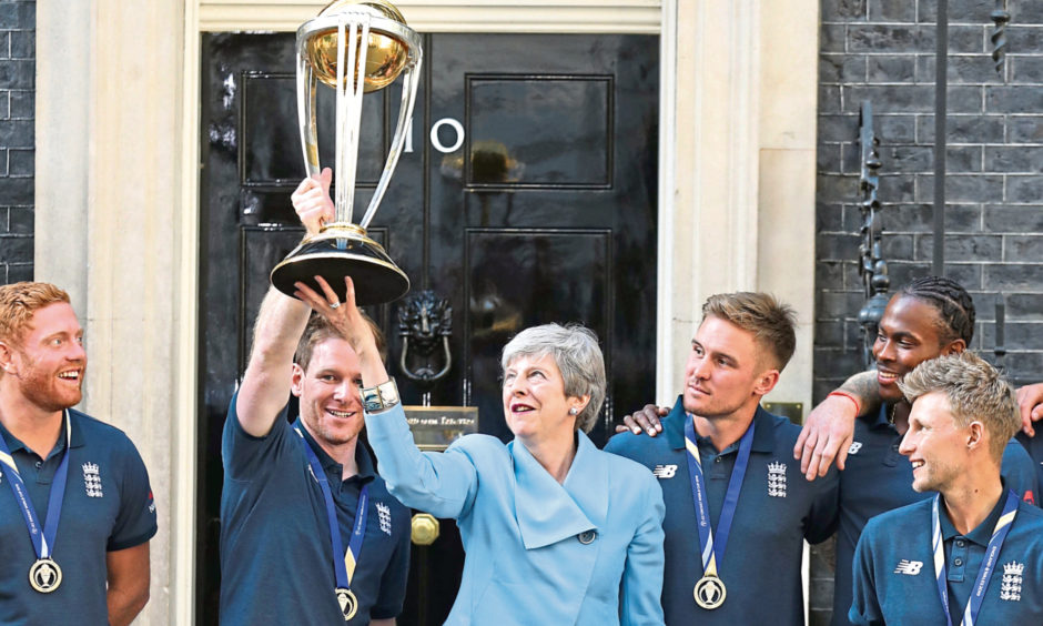 Prime Minister Theresa May with England cricket captain Eoin Morgan and members of the team with the trophy outside Downing Street, London, ahead of a reception hosted by the Prime Minister at Downing Street, London, to celebrate England's victory in the ICC World Cup.