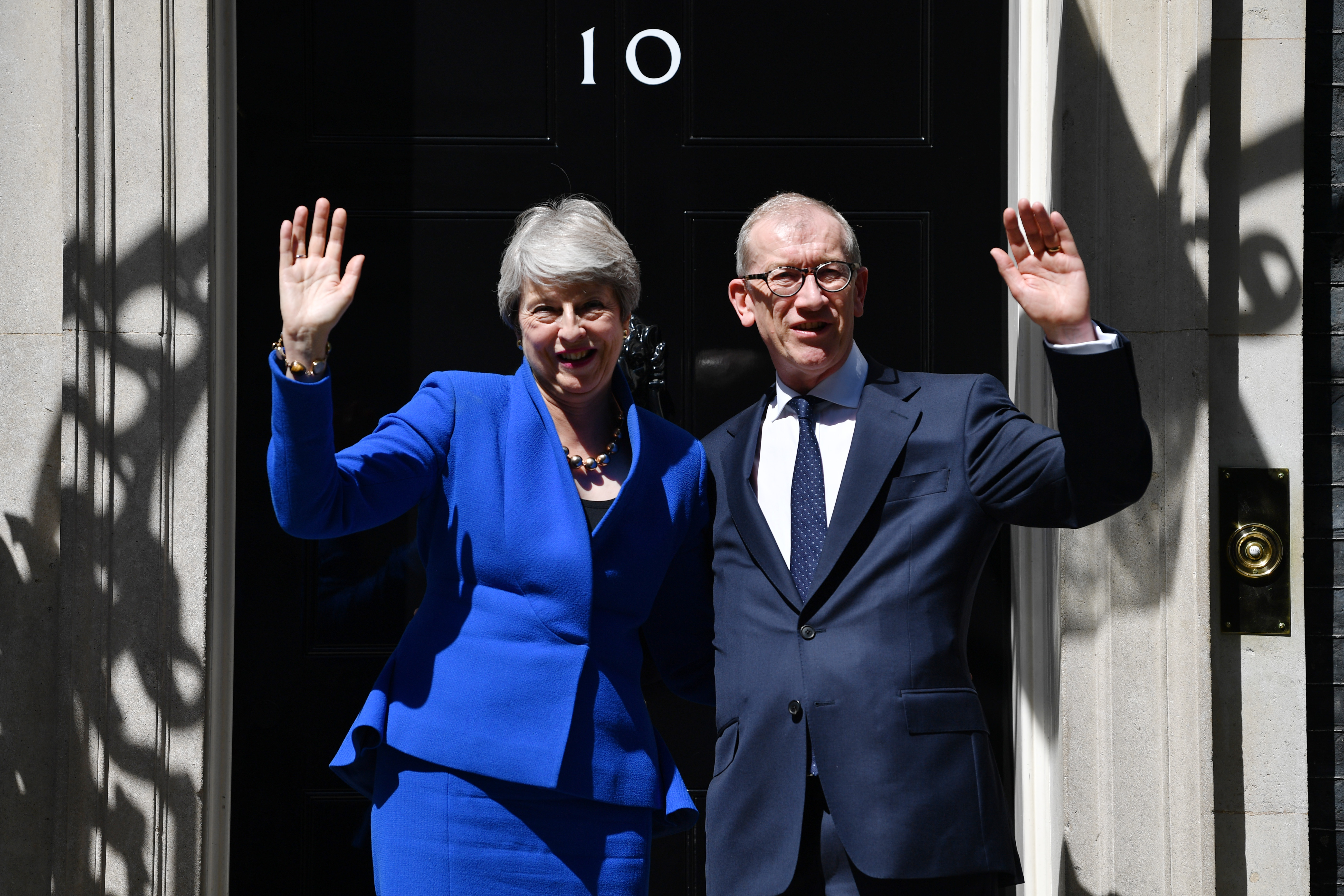Theresa May waves to the world's media beside husband Philip May from outside 10 Downing Street