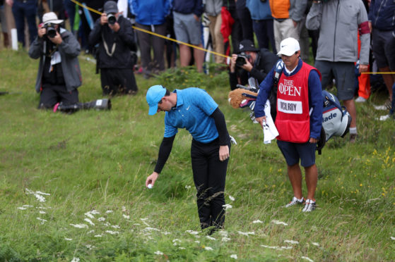 Rory McIlroy takes his drop after hitting out of bounds at the first during his 79 at Portrush.