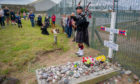 A piper plays at Bamse's grave.
