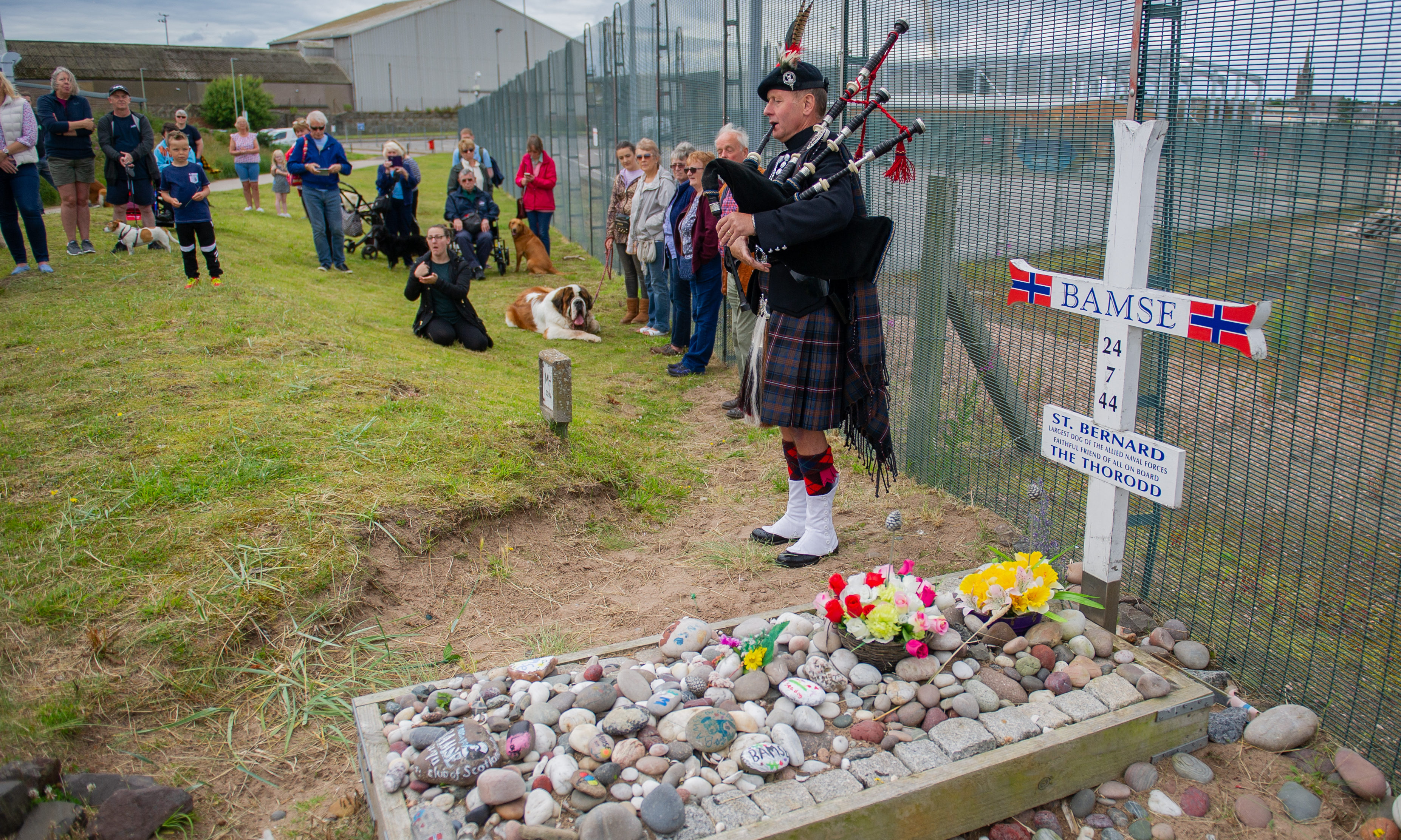 A piper plays at Bamse's grave to mark 75 years since his passing in 2019.