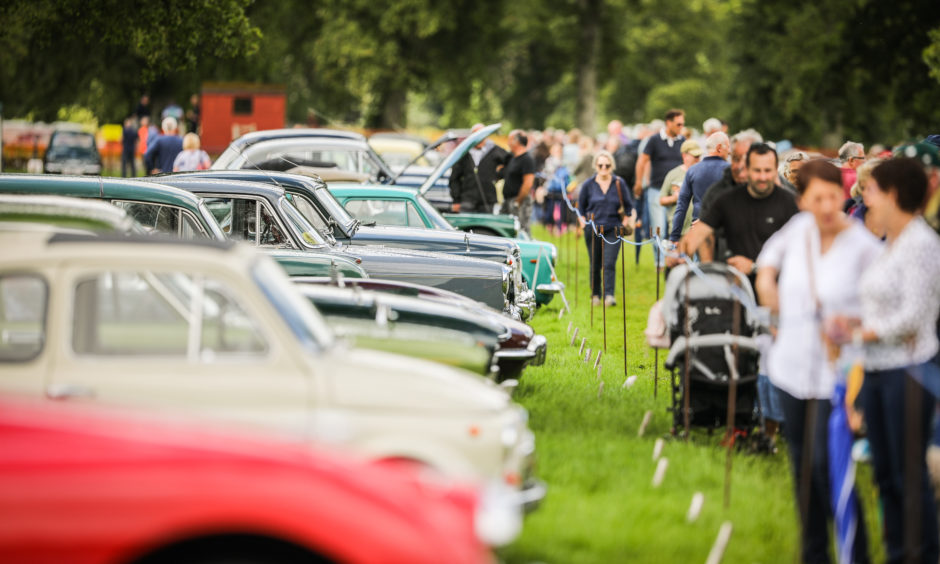 The crowds admire the vintage vehicles on display.