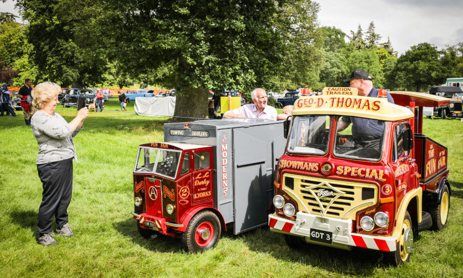 Visitors admire the vintage vehicles on display.