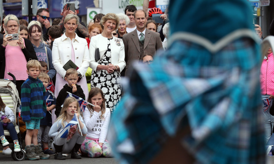 The Earl and Countess of Forfar watch a highland dancing performance as they arrive on Castle Street in Forfar.