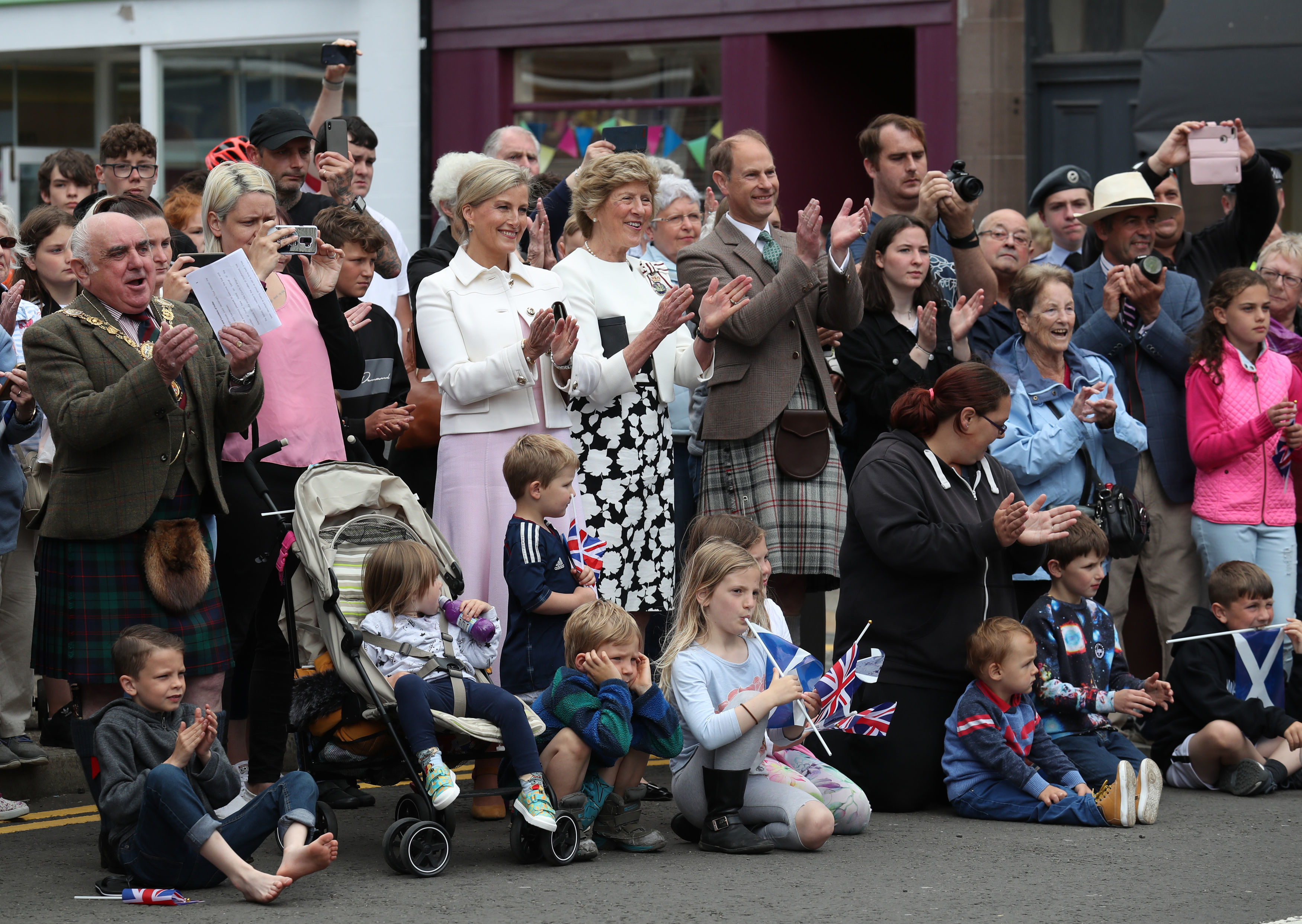 Lord Lieutenant Mrs Osborne applauds a Highland Dancing display with the new Earl and Countess of Forfar on their first visit to the town in July.
