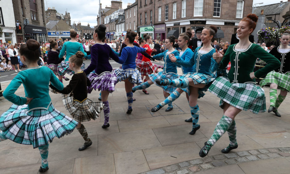 Highland dancers perform for The Earl and Countess of Forfar  in Castle Street in Forfar.