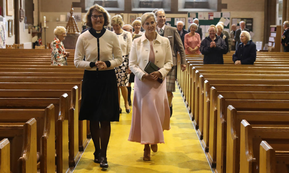 The Earl and Countess of Forfar alongside Rev Elaine Garman inside the church where the Queen mother was confirmed as they view the register of Confirmations showing the Queen Mothers name in Forfar.