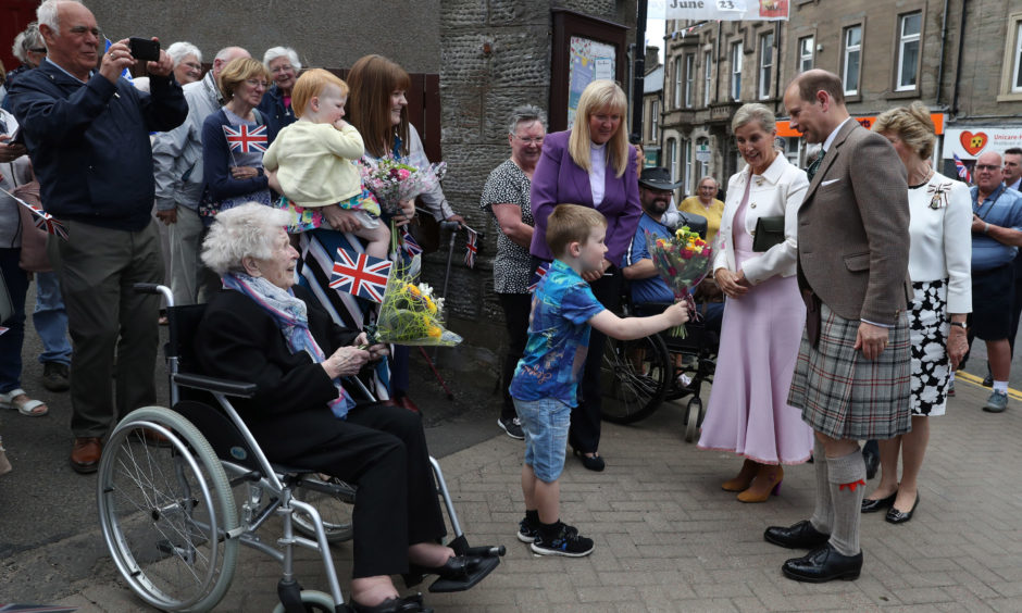 Jack Miles presents a posy to The Earl and Countess of Forfar during a walkabout in Forfar.