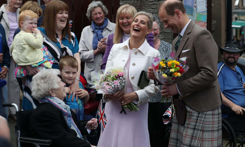 The Earl and Countess of Forfar laugh alongside May Balfour (101) during a walkabout in Forfar.